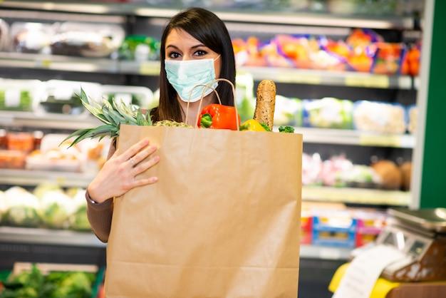 Donna mascherata in possesso di un sacchetto di cibo sano