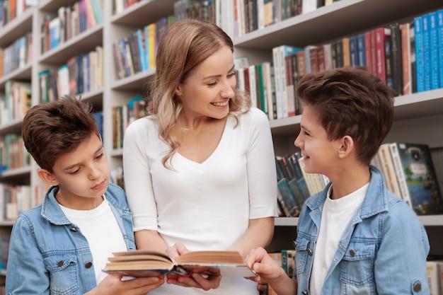 Donna matura adorabile che gode leggendo un libro ai suoi piccoli figli gemelli svegli
