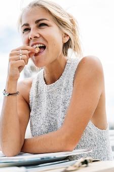 Donna matura bionda che mangia una noce che si siede su un terrazzo