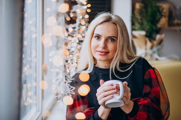 Donna matura che beve il caffè vicino alla finestra