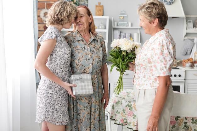 Donna matura che esamina sua madre e sua figlia che si abbracciano