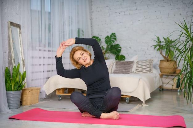 Donna matura che fa yoga che si siede sulla stuoia a casa, concetto sano di stile di vita che si siede a casa