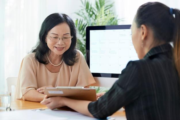 Donna matura che parla con agente assicurativo