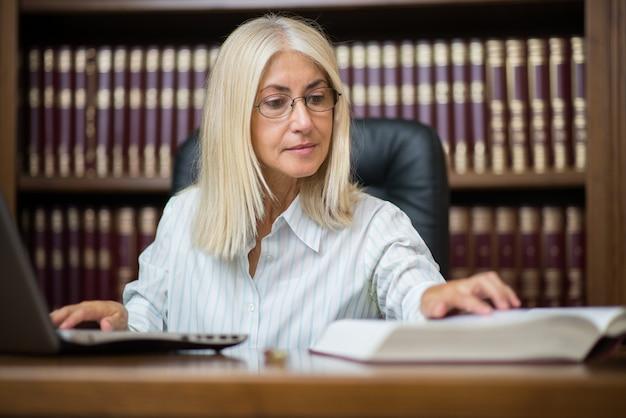 Donna matura che per mezzo del suo computer portatile mentre leggendo un libro