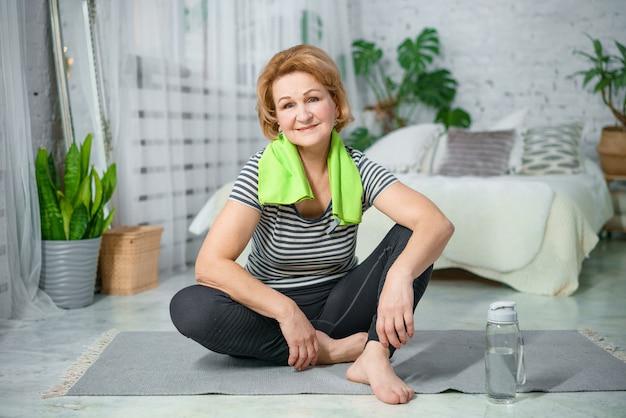 Donna matura che riposa sulla stuoia di esercizio dopo l'allenamento di forma fisica