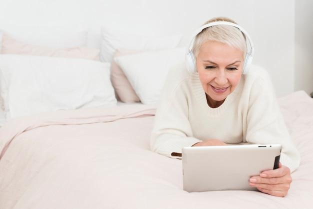 Donna matura che sorride e che esamina compressa a letto con lo spazio della copia