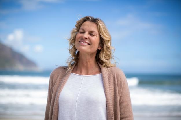 Donna matura che sta sulla spiaggia