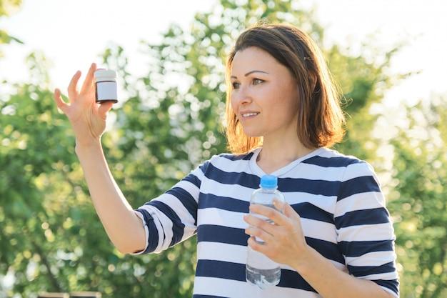 Donna matura con bottiglie di farmaci di medicina, vitamine, integratori