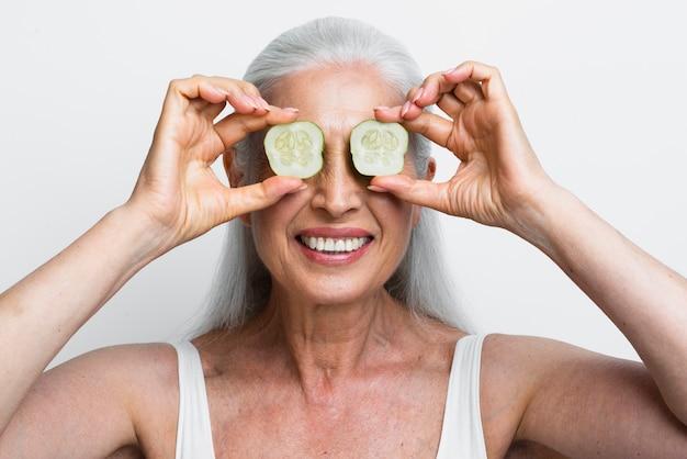 Donna matura con fette di cetriolo sui suoi occhi