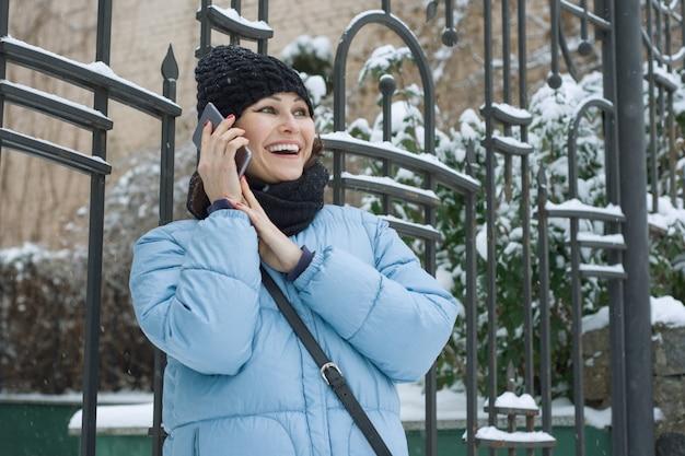 Donna matura con il cellulare in una giornata nevosa