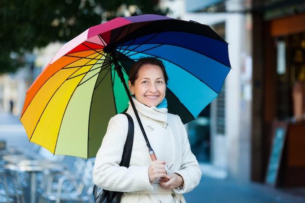 Donna matura con l'ombrello in autunno