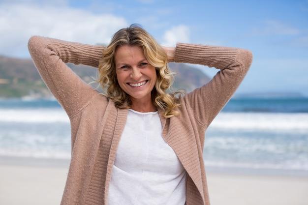 Donna matura con le mani dietro la testa in piedi sulla spiaggia