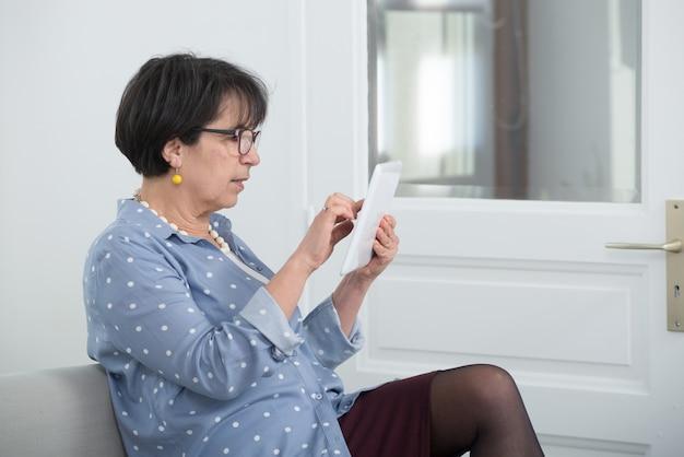 Donna matura del brunette che si siede sul sofà per mezzo della compressa digitale