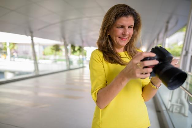 Donna matura felice del fotografo che per mezzo della macchina fotografica all'aperto