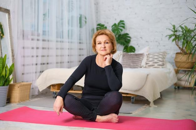 Donna matura in una tuta nera facendo yoga seduto sul tappeto a casa, sullo sfondo di un letto e vasi di piante verdi, stile di vita sano concetto seduto a casa