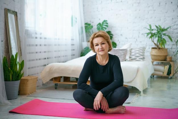Donna matura in una tuta nera facendo yoga seduto sul tappeto a casa, sullo sfondo di un letto e vasi di piante verdi,
