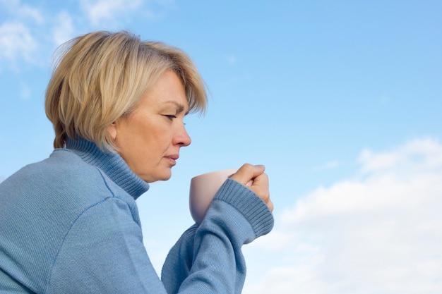 Donna matura senior in maglione caldo che beve caffè o tè caldo da una tazza all'aperto.