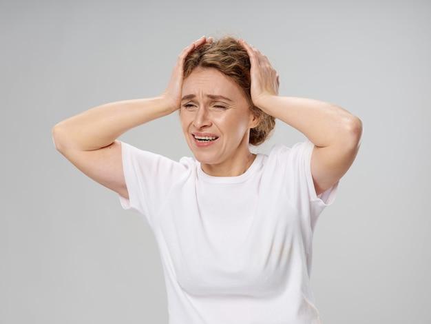 Donna matura sollecitata con le mani sulla testa
