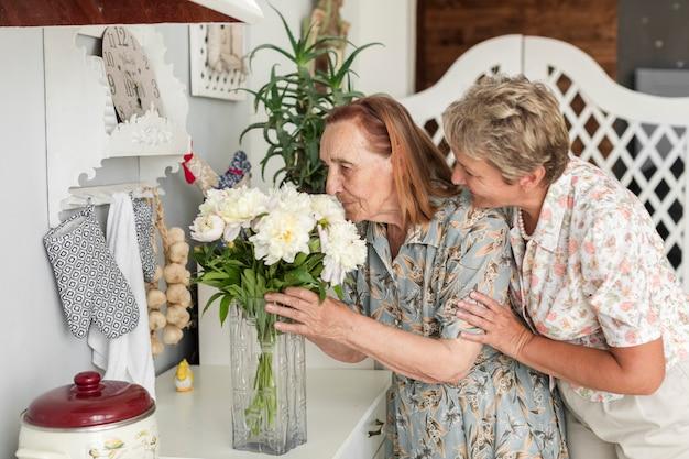 Donna matura sorridente che esamina sua madre che odora il vaso di fiori bianchi a casa