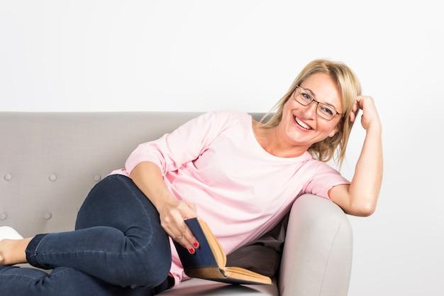 Donna matura sorridente che si appoggia il libro della tenuta del sofà a disposizione contro il contesto bianco