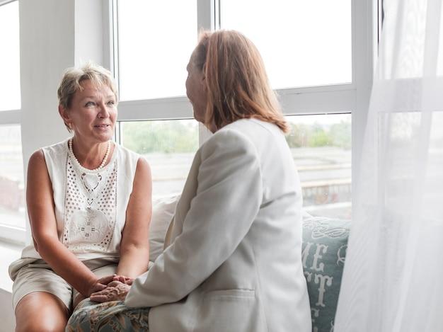 Donna matura sorridente che si siede con sua madre sul davanzale della finestra