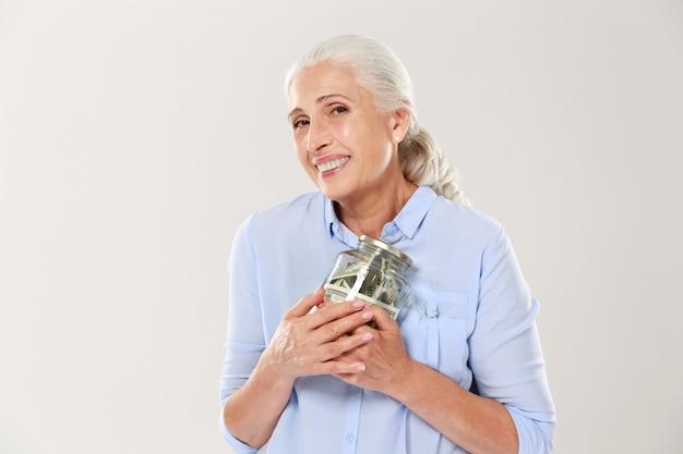 Donna matura sorridente felice che abbraccia il suo barattolo di vetro con i dollari
