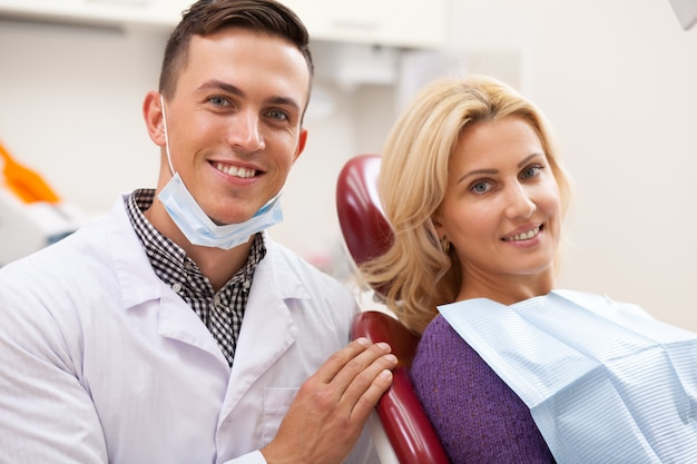 Donna matura splendida e il suo dentista maschio che sorridono felicemente alla macchina fotografica alla clinica dentale.