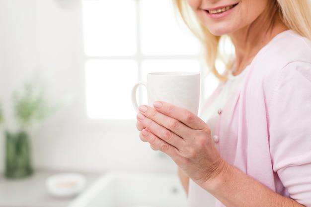Donna matura sveglia del primo piano che tiene una tazza