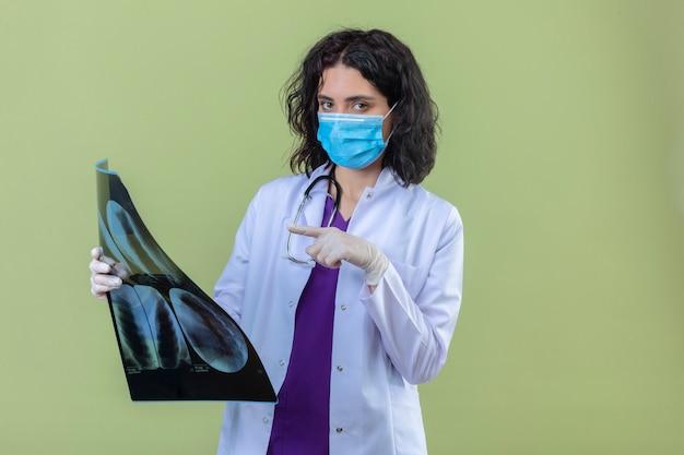 Donna medico che indossa camice bianco con uno stetoscopio in maschera protettiva medica tenendo i raggi x dei polmoni puntando ad esso con il dito con faccia seria sul verde isolato