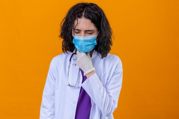 Donna medico indossa camice bianco con uno stetoscopio in maschera protettiva medica toccando collo doloroso mal di gola per zolla influenzale e infezione in piedi su arancione isolato