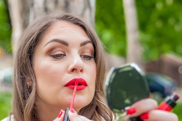 Donna mettendo, correggendo il rossetto rosso lip gloss. bella donna alla moda bruna corretta compongono