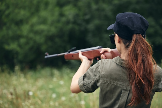 Donna militare che tiene una tuta verde di vista posteriore dell'obiettivo di caccia della pistola