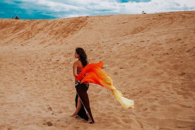 Donna misteriosa con il vestito d'oro che cammina sulla sabbia dorata delle dune del deserto al tramonto