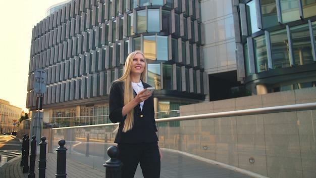 Donna moderna che cammina sulla strada urbana contemporanea. lass usando il telefono e camminando sulla strada asfaltata della città contemporanea con nuove costruzioni di uffici al sole.