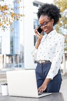 Donna moderna che lavora al computer portatile e che parla sopra il telefono