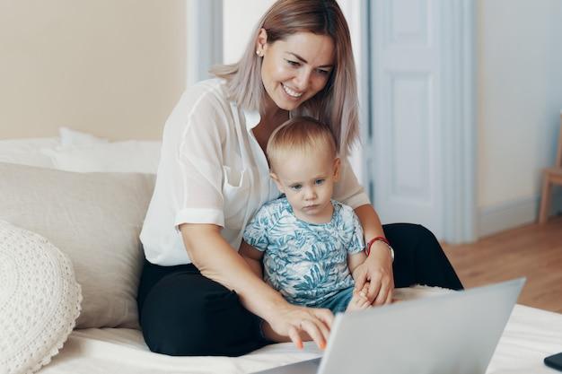 Donna moderna che lavora con il bambino. concetto multi-tasking, freelance e maternità