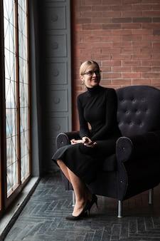 Donna moderna che si siede sul divano
