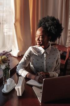 Donna moderna dell'angolo alto allo scrittorio che lavora al suo computer portatile