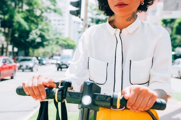 Donna moderna in una città con uno scooter elettrico