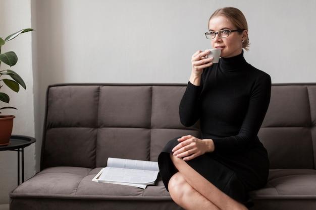 Donna moderna sul divano a bere il caffè