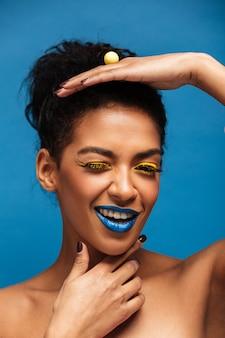 Donna mulatta fantasia verticale con trucco colorato e capelli ricci in panino in posa sulla macchina fotografica con sguardo giocoso isolato, sopra la parete blu