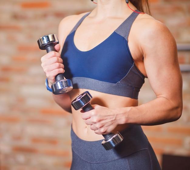 Donna muscolare con l'ente perfetto in manubri della tenuta degli abiti sportivi nella palestra contro il muro di mattoni.
