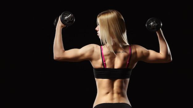 Donna muscolare sulla sua schiena di sollevamento pesi su sfondo nero