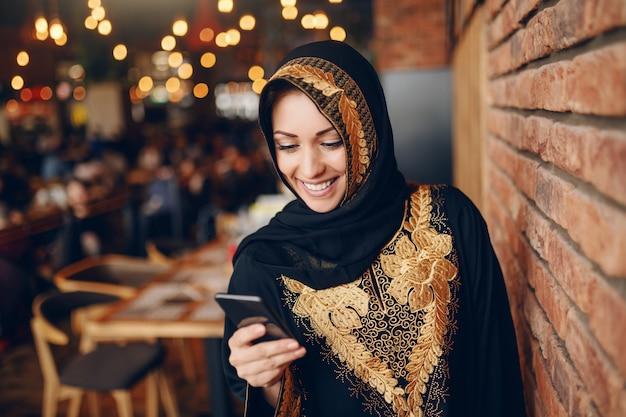 Donna musulmana affascinante allegra in abaya facendo uso dello smart phone per la lettura o la scrittura del messaggio mentre sedendosi nel self-service.