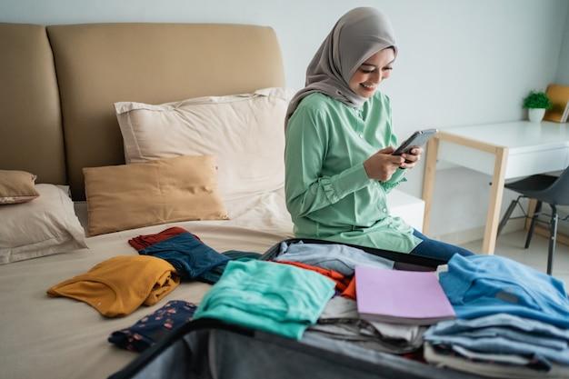 Donna musulmana asiatica che per mezzo del suo telefono cellulare con la valigia piena