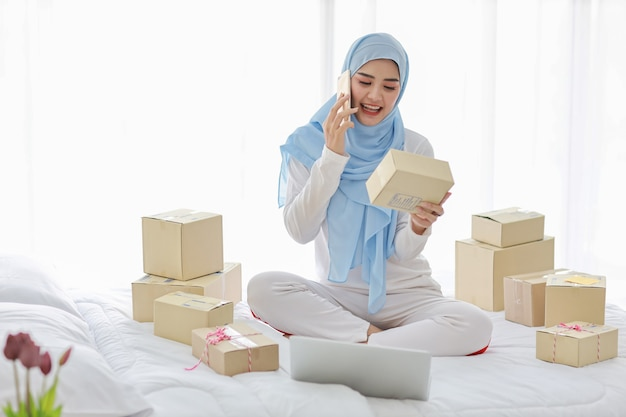Donna musulmana asiatica con un sacco di scatole a letto