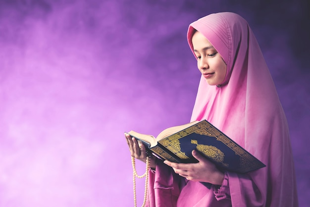 Donna musulmana asiatica in un velo che tiene le perle di preghiera e che legge il corano con uno sfondo colorato