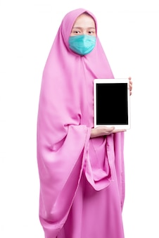 Donna musulmana asiatica in un velo e indossa una maschera antinfluenzale che mostra uno schermo bianco tablet
