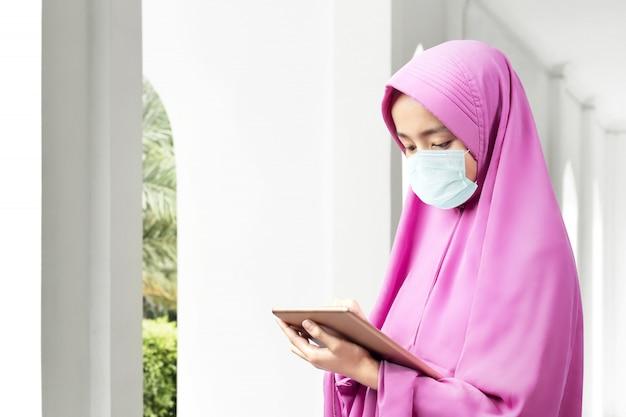 Donna musulmana asiatica in un velo e indossa una maschera antinfluenzale facendo uso della compressa