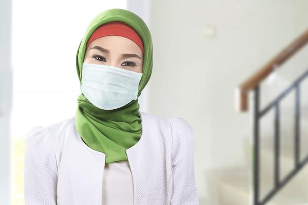 Donna musulmana asiatica in un velo e indossa una maschera antinfluenzale